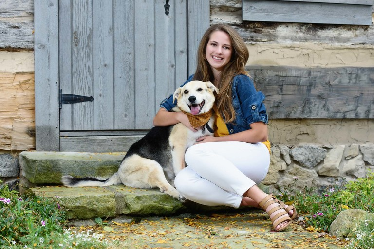 Senior girls posed with her dog on steps